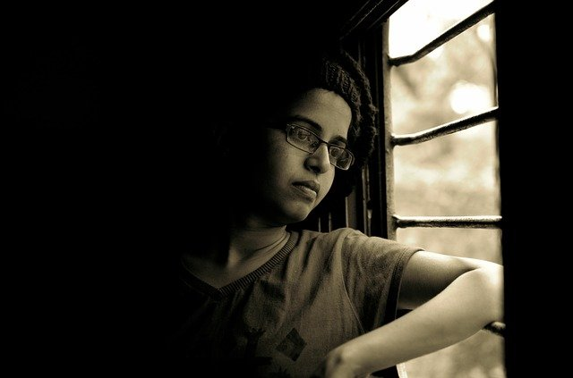 woman looking through window in jail